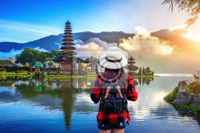 Bild Woman traveler with backpack looking to pura ulun danu bratan temple in Bali, indonesia.