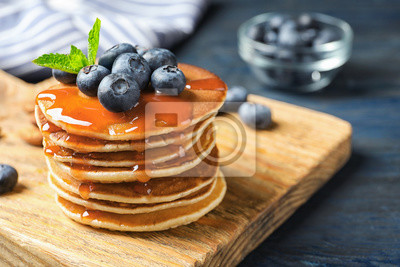 Bild Wooden board with pancakes, syrup and blueberries on table, closeup