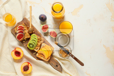Bild Wooden board with tasty sweet sandwiches on table