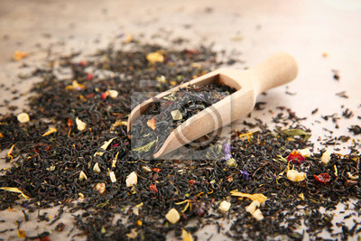 Bild Wooden scoop and scattered dry tea leaves on table, closeup