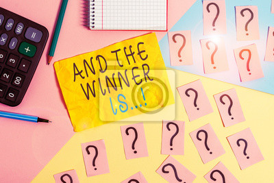 Bild Writing note showing And The Winner Is. Business concept for announcing who got first place at competition or exam Mathematics stuff and writing equipment above pastel colours background