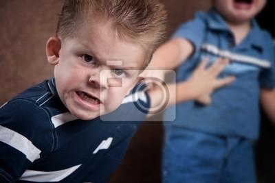 Bild Wütend kleiner Junge starrte und den Kampf mit seinem Bruder