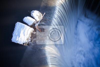 Steine bedeckt mit Schnee am Rande eines Wasserfalls