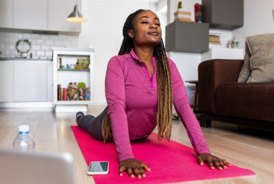 Bild Young african america woman at home doing exercise in front of open laptop, repeating instructions by professional online fitness trainer.