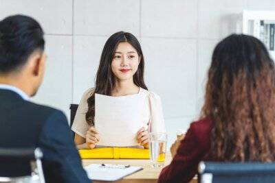 Bild Young Asian woman graduate holding the resume document and preparing to two manager before start to job interview with positive motion in meeting room,Business Hiring new member concept