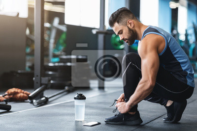 Bild Young athlete tying sneakers laces at gym