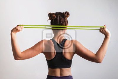 Bild Young athletic woman doing exercises with fitness rubber band