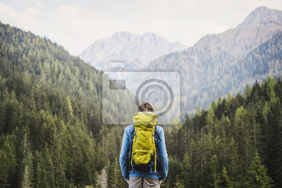 Bild Young backpacking man traveler enjoying nature in Alps mountains. Travel and active lifestyle concept.