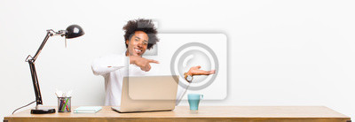 Bild young black businessman smiling, feeling happy, carefree and satisfied, pointing to concept or idea on copy space on the side on a desk