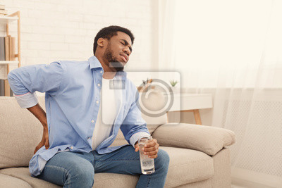Bild Young black man with back pain at home
