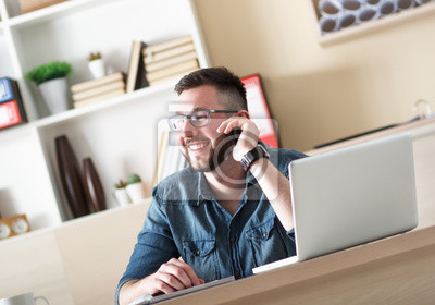Bild Young businessman talking on phone and working with laptop