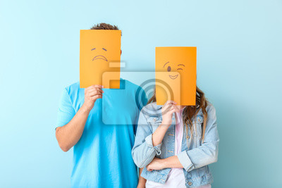 Bild Young couple hiding faces behind emoticons against color background