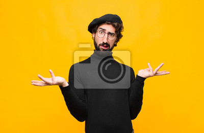 Bild young french artist man shrugging with a dumb, crazy, confused, puzzled expression, feeling annoyed and clueless against orange wall