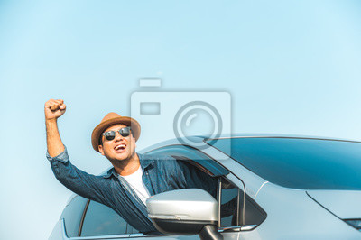 Bild Young handsome asian man driving car to travel on his holiday vacation time with beautiful blue sky.