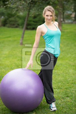 Young happy woman with fitness ball, outdoor