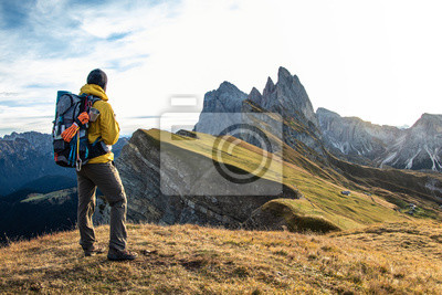 Bild Young man hiking at Seceda mountain peak at sunrise. Backpack, yellow jacket, boots, beanie. Traveling to puez Odle, Dolomites, Trentino, Italy.