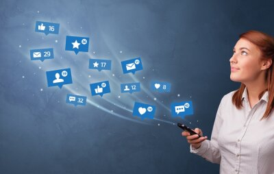 Bild Young person using phone with flying social media icons around