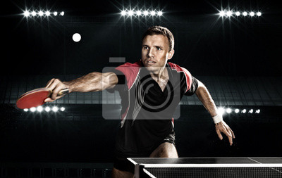 Young sports man tennis-player in play on black background.