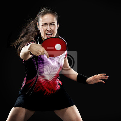 Young sports woman tennis-player in play on black background