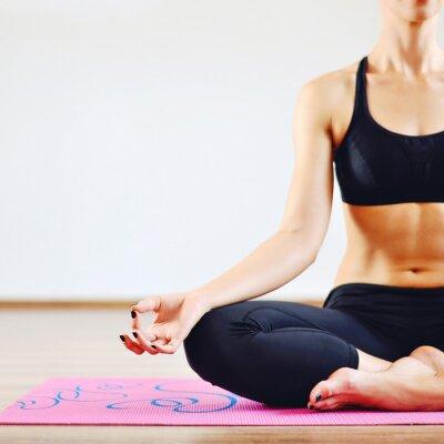 Bild Young woman doing yoga indoors - body part