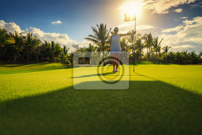 Young woman golfer standing on tropical golf course, sunset, Dominican Republic