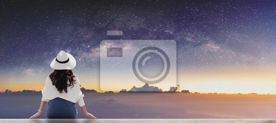 Bild Young woman in white hat looking at horizon with sky full of stars at dawn