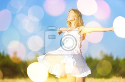 Bild Young woman on field under sunset light