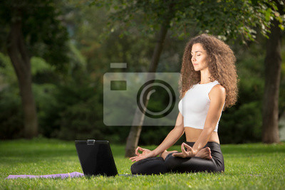 Young woman sitting in a yoga position with a laptop