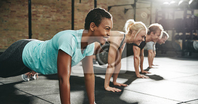 Bild Young woman smiling while doing pushups in an exercise class