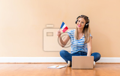 Bild Young woman with French flag using a laptop computer against a big interior wall