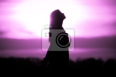 Bild Youth woman soul at pink sun meditation awaiting future times. Silhouette in front of sunset or sunrise in summer nature. Symbol for healing burnout therapy, wellness relaxation or resurrection