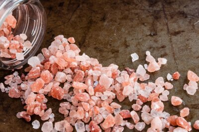 Bild Zerstreute Himalaya-rosa Salzkristalle aus Glasflasche auf rostigen Metall Hintergrund
