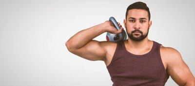Zusammengesetztes Bild des muskulösen ernsten Mannes, der eine Kettlebell anhält