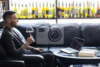 Bild Zuversichtlich scharf gekleideter Mann mit Glas Wein