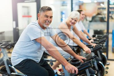 Bild Zuversichtlich Senioren auf Übungsfahrräder in Spinning-Klasse in der Turnhalle