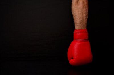 Zwei Hände in roten Boxhandschuhen in der Seite des Rahmens auf einem schwarzen Hintergrund, leeren Raum