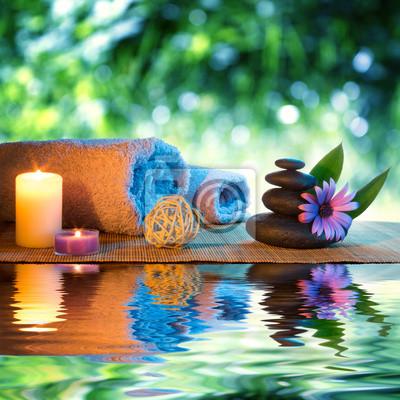 zwei Kerzen und Handtücher schwarzen Steinen und lila Gänseblümchen auf dem Wasser