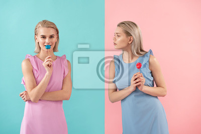 Bild Zwei Mädchen, die Bonbons auf Stock halten. Ein Blick auf einen anderen mit Neid. Isoliert auf blauem und rosa Hintergrund