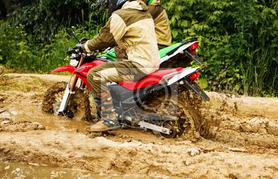 Bild Zwei Männer auf einem Motorrad reitet durch den Schlamm