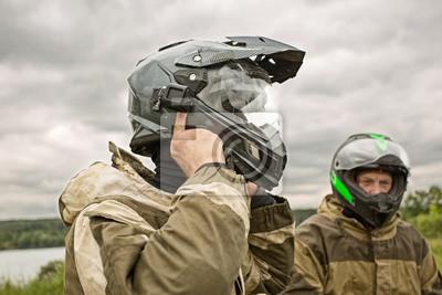 Bild Zwei Männer, die draußen Motorradsturzhelme und -uniformen tragen.