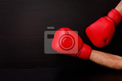 Zwei männliche Hände in rote Boxhandschuhe auf einem schwarzen Hintergrund auf der Seite des Rahmens, Platz für Text