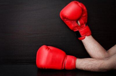 Zwei männliche Hände in roten Boxhandschuhen auf einem schwarzen Hintergrund, Platz für Text