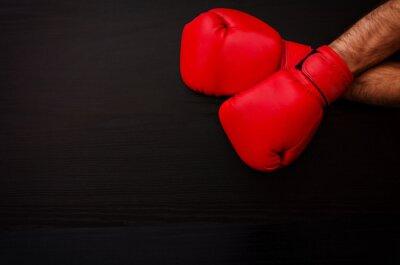 Zwei männliche Händen in roten Boxhandschuhen auf einem schwarzen Hintergrund in der Ecke des Rahmens, Platz für Text