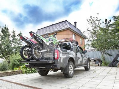 Bild Zwei Schmutzfahrradmotorräder auf der Rückseite des Camo-LKW auf der Fahrstraße.
