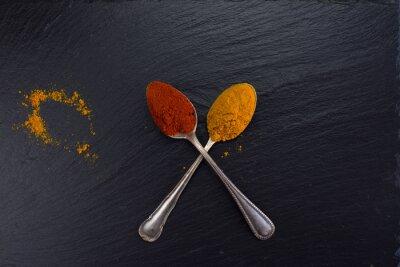 Bild Zwei Vintage Löffel mit Gewürzen Curry und Paprika auf schwarzem Hintergrund.