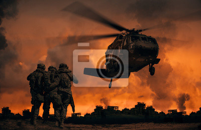 Fototapete 2 soldiers helping wounded soldier between dust in battle field to board the helicopter