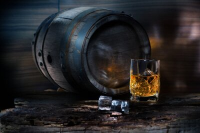 Fototapete A glass of whiskey with ice on background barrel