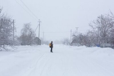 Fototapete A rustic man is walking down the street in winter with a yellow backpack. Snow blizzard.