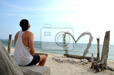 A single man sits alone on the beach in front of a big heart. He looks up to the sky. Perhaps he is sad, depressed and alone. Perhaps he just waits for his girlfriend.
