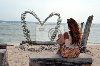 A young single woman is sitting on the beach in front of a big heart without a relationship or a partner / boyfriend. This makes her sad, because she is alone / lonely and searches for love.